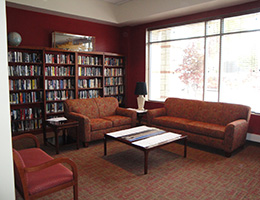 red interrior with sofas and a small library