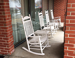 four white rocking chairs sitting outside
