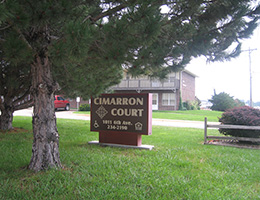cimarron court outdoor sign next to nice green trees