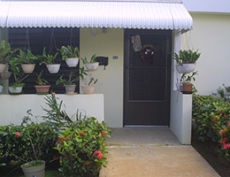 front of a door with hanging potted plants and an awning