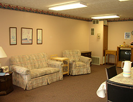 living area with a television, couches and chairs lining the walls