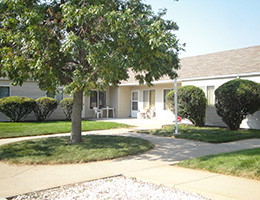 Great Plains community showing a house with a nice walking path out front and grass, a tree and nicely kept bushes
