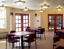 Nicely lit community room with several tables and chairs