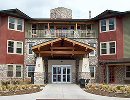 Harvest Pointe grand entrance with a rustic wood roof and large pillars holding it up