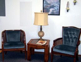 Sitting area with two chairs and a table in between with a lamp and a magazine