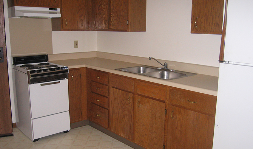 Apartment kitchen with stove, refrigerator, wood cabinets and open countertops