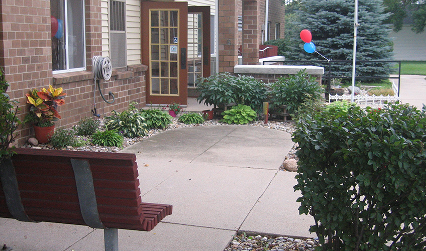 Lakeview Manor sitting area surrounded by a walking path, entrance to the community and nicely kept garden area