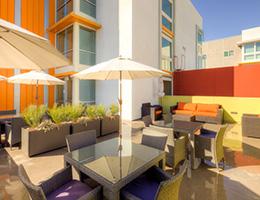 Las Alturas rooftop patio with seating areas, planters and shade umbrellas