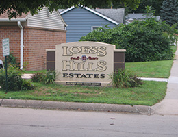 Loess Hills Estates sign surrounded by greenery and homes in the background