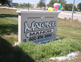 Malone Manor sign out front in the grass