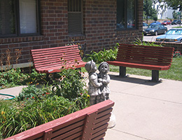 Malone Manor seating area outside with a statue of children and greenery around it