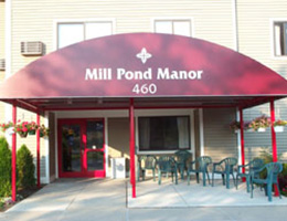 front of the mill pond manor building with a red awning and outdoor furniture