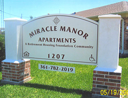 Miracle Manor Apartments sign on brick posts