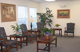 waiting room with paintings on the wall and a plant centerpiece