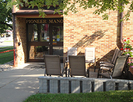 Pioneer Manor front entrance with sliding doors and seating out front
