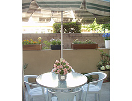 resident patio with table, chairs, umbrella and bouquet of flowers