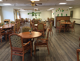 Resident dining area with wood floors and decorations on the walls