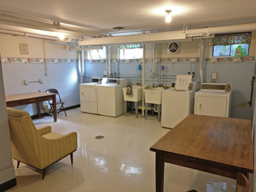 laundry room with tables, chairs and two sets of washers and dryers