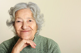 smiling elderly woman with chin on hand
