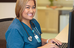 smiling nurse with a stethoscope sitting at a computer