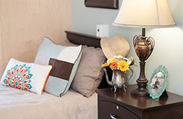 nice pillows on  a bed with a nice bedside table