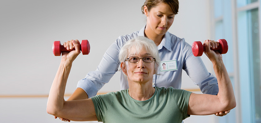 female resident lifting small hand weights while working with a trainer