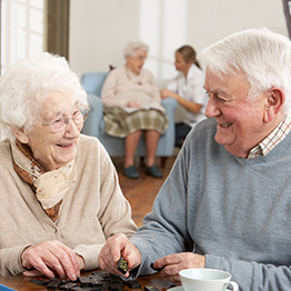 elderly couple smiling together while playing dominos