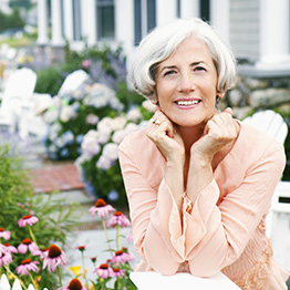 Woman sitting outside in flower garden smiling