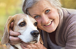 smiling woman hugging a dog outside
