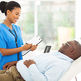 female nurse holding a clipboard speaking with a male resident that is lying down