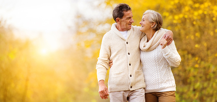 couple dressed warmly taking a walk on a sunny Autumn day