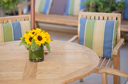 small sunflowers sitting on an outside table in a vase