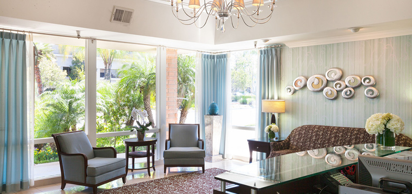 beautiful lobby style area with a chandelier, sofa, chairs and glass windows