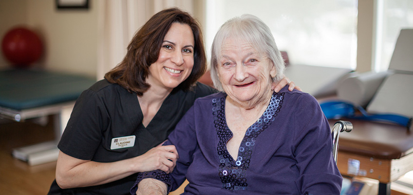 elderly woman in a wheelchair and a staff member smiling