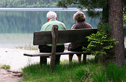 a man and a woman seated outside on a bench overlooking the lake