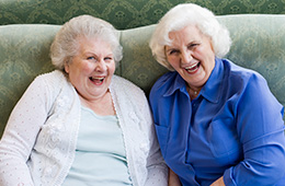 Two elderly ladies sitting on a bench together smiling