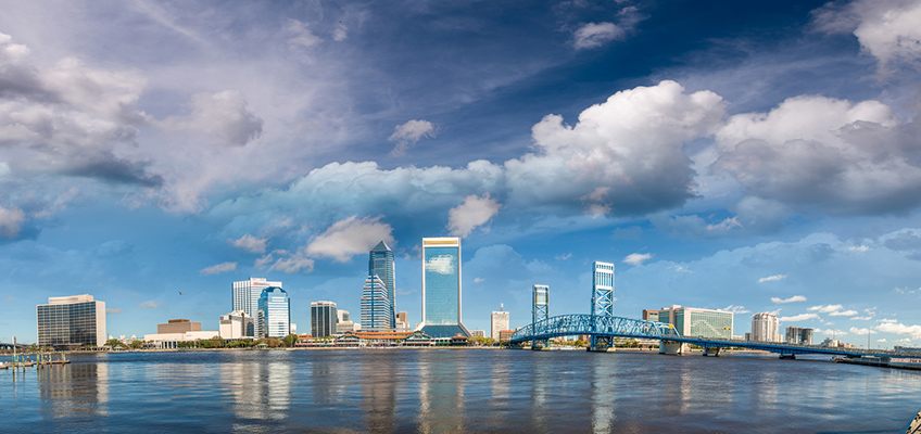 Jacksonville, Florida area with sky rise buildings, a bridge going over the water and white puffy clouds in the sky above