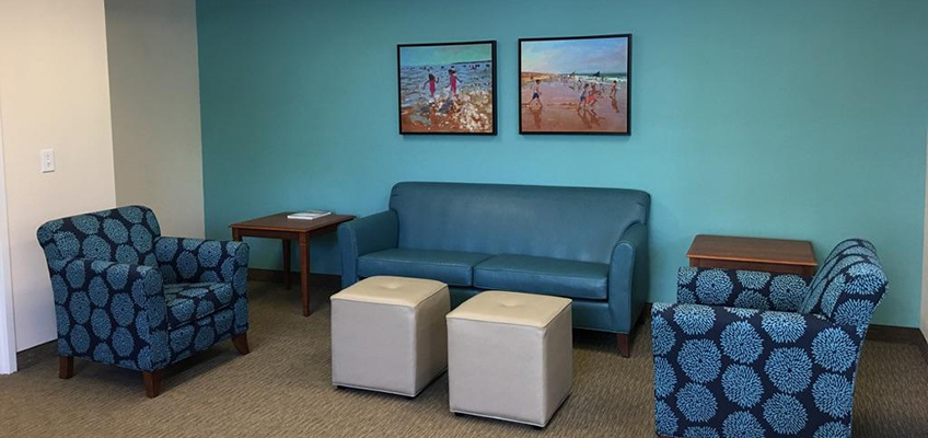 The Towers of Jacksonville sitting area with a couch and two chairs on either side of it along with end tables and cushions in front of the couch for lougning