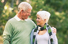 Elderly couple walking through a park together smiling at each other