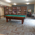 Activity room with books and a pool table along with a shelf of games to play