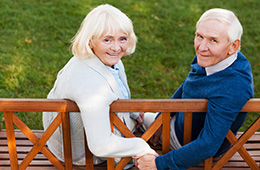 Elderly couple sitting together on a wood bench holding hands with grass in the background