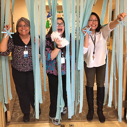 three people under blue streamers and popsicle stick starfish