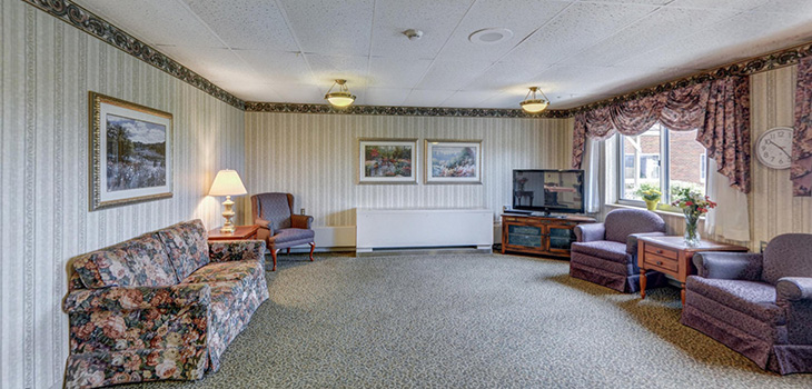 Minot carpeted waiting area with upholstered couch and chairs and a flat screen TV