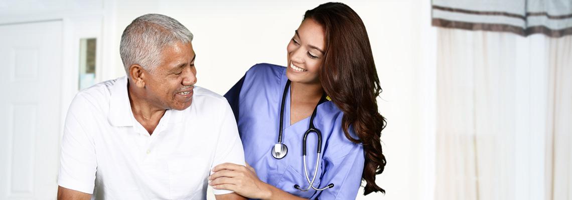 A nurse leaning toward a patient smiling
