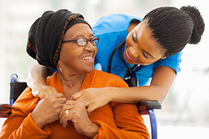 Nurse with resident in a wheelchair leaning in smiling