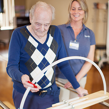 elderly man in sweater doing rehabilitation exercises