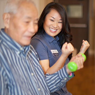 smiling therapist helping resident with weights