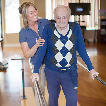 man using parallel bars for walking therapy