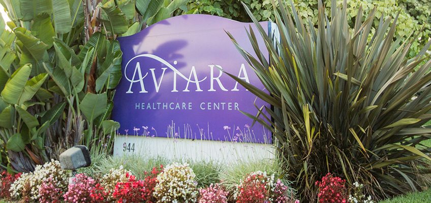 nice aviara healthcare center sign with beautiful plants surrounding it