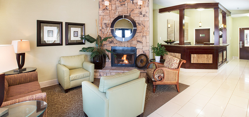 lobby with a fireplace and mirror on the mantle and chairs around it